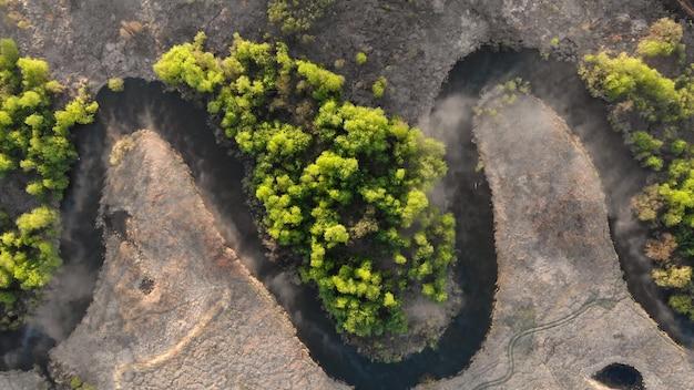 Een kronkelende rivier in het midden van een dicht bos. bosrivier vanuit vogelperspectief. bovenaanzicht van het reservaat. de camera gaat langzaam omlaag