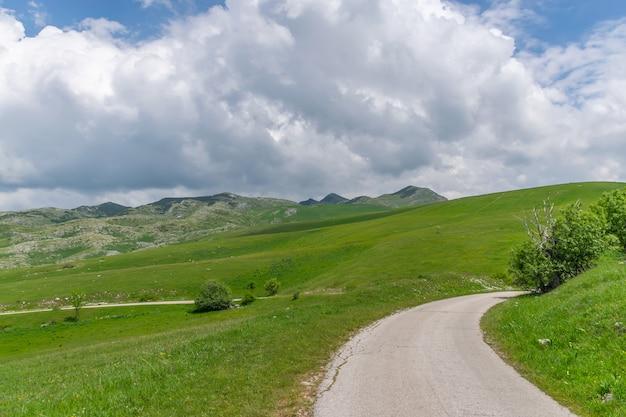 Een kronkelende smalle weg leidt door pittoreske weiden en bergen