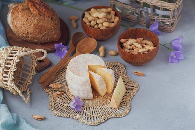 Een krop verse biologische kaas geserveerd met brood, noten, witte wijn en zomerbloemen. gezond en biologisch voedselconcept.