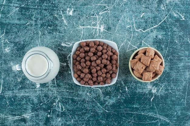 Een kruik melk en granen in kommen, op de blauwe achtergrond. hoge kwaliteit foto