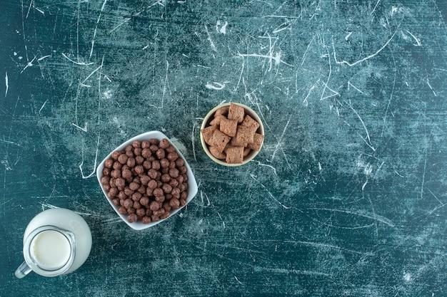 Een kruik melk en granen in kommen, op de blauwe tafel.