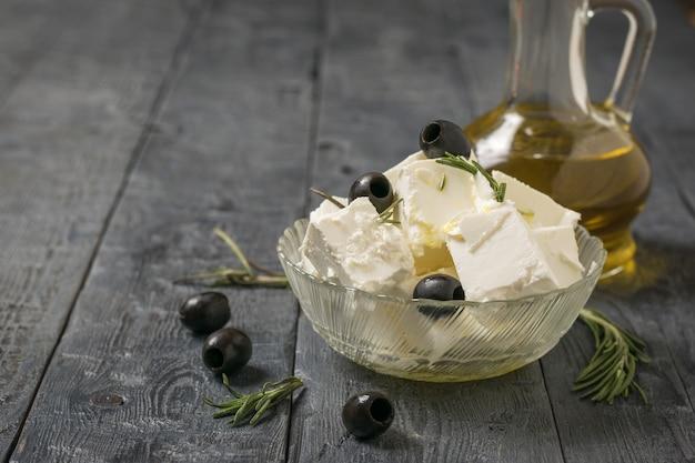 Een kruik olijfolie en fetakaas met olijven op een houten tafel. natuurlijke kaas gemaakt van schapenmelk.