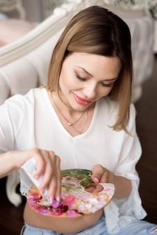 Een kunstenaar schildert beeld op canvas met olieverf in haar atelier