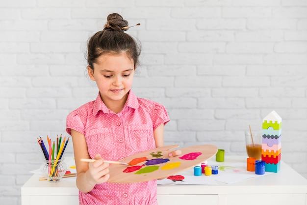 Een kunstenaar van het kindmeisje die de waterverf op palet mengt