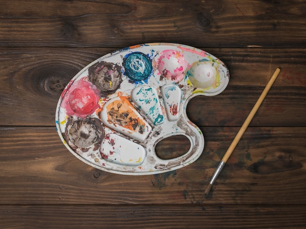 Een kunstenaarspalet en een penseel op een houten tafel. plat leggen.