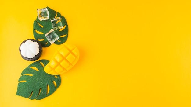 Een kunstmatige monstera vertrekt; mangosteen; ijsblokjes en mongo slice tegen gele achtergrond