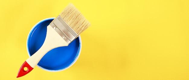 Een kwast wordt op een blauw blikje geplaatst. met een gele achtergrond
