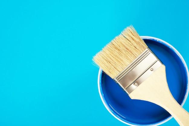 Een kwast wordt op een verfblik geplaatst. met blauwe achtergrond