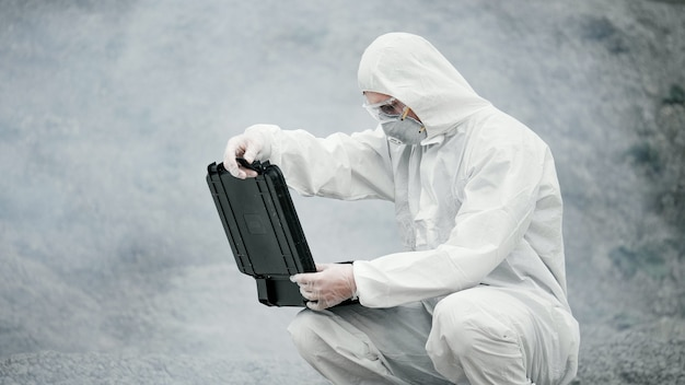 Een laboratoriumtechnicus in een masker en een chemisch beschermend pak opent een gereedschapskist op het droge