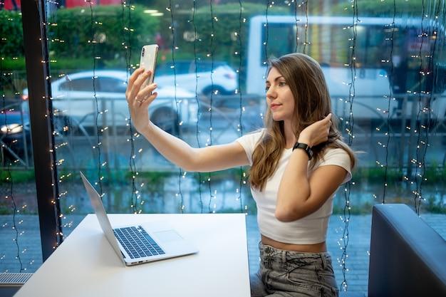 Een lachend freelancermeisje neemt een selfie aan de telefoon of voert een videogesprek, een werkdag van een vrije jonge vrouw of een student met een laptop