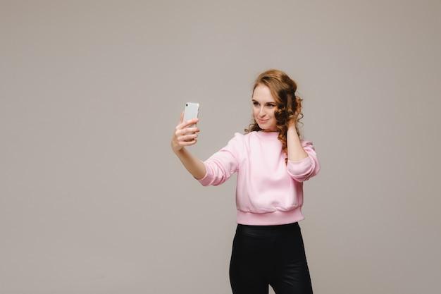 Een lachend gelukkig meisje in een roze blouse neemt een selfie op een smartphone op een grijze achtergrond.