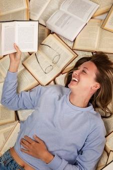 Een lachend jong meisje in een blauwe trui en spijkerbroek ligt op een stapel open boeken lezen