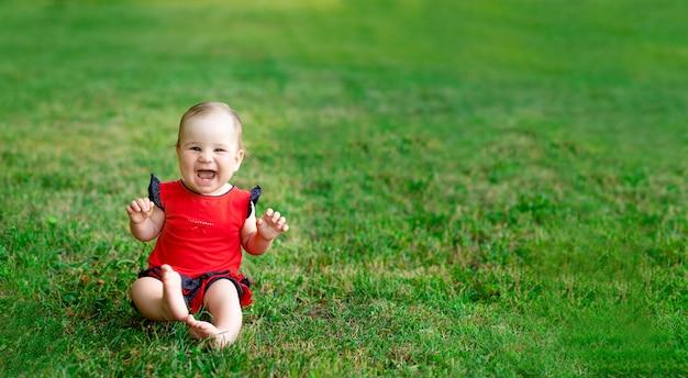 Een lachend kind in de zomer op het groene gras in een rode bodysuit in de stralen van de ondergaande zon verheugt zich, een bannerplaats voor de tekst
