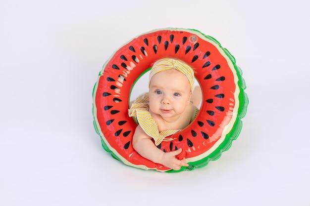 Een lachend kind in een zwembroek met een zwemring in de vorm van een watermeloen ligt.