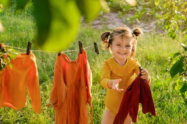 Een lachend meisje draagt kleren in haar handen om ze aan een waslijn te hangen om te drogen