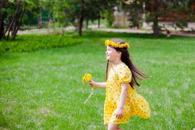 Een lachend meisje in een gele jurk en gele bloemen met haar ogen dicht geniet van een warme zonnige dag in ...