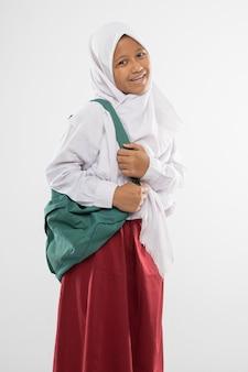Een lachend meisje in een gesluierd basisschooluniform met een schooltas