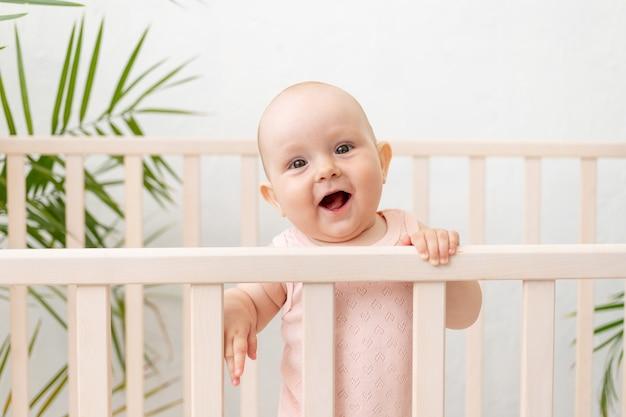 Een lachend meisje in een wieg in een roze bodysuit voor zes maanden staat aan de kant en lacht