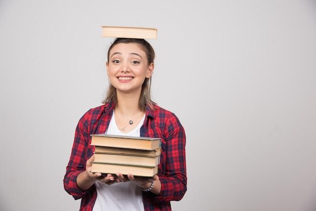 Een lachend meisje met een boek op haar hoofd