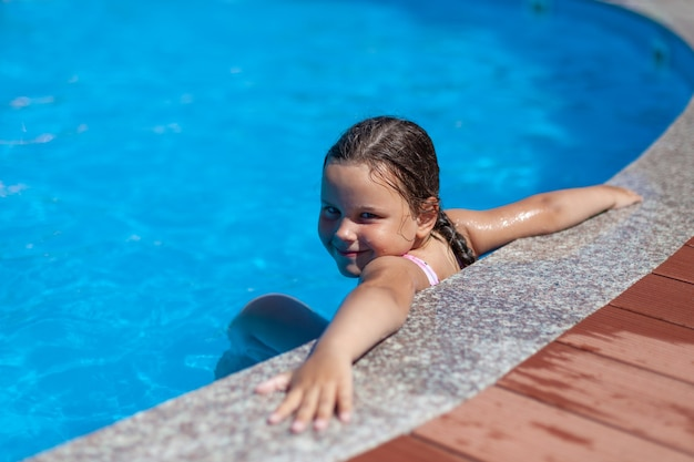 Een lachend vijfjarig meisje legde haar handen wijd op de rand van het zwembad bij het hotel het concept van een ...