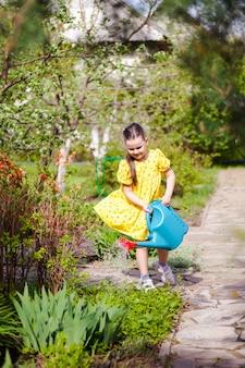 Een lachend vrolijk meisje in een gele jurk die in de wind vliegt, geeft jonge bloemen water uit een blauwe wat...