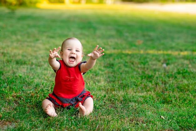 Een lachende baby in de zomer op het groene gras in een rode bodysuit in de ondergaande zon verheugt zich, ruimte voor tekst