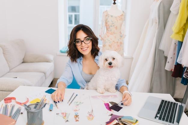 Een lachende brunette meisje in een blauw shirt zit aan de tafel in de atelierstudio. ze werkt met schetsen en stofstalen. ze heeft een leuke hond op de knieën.
