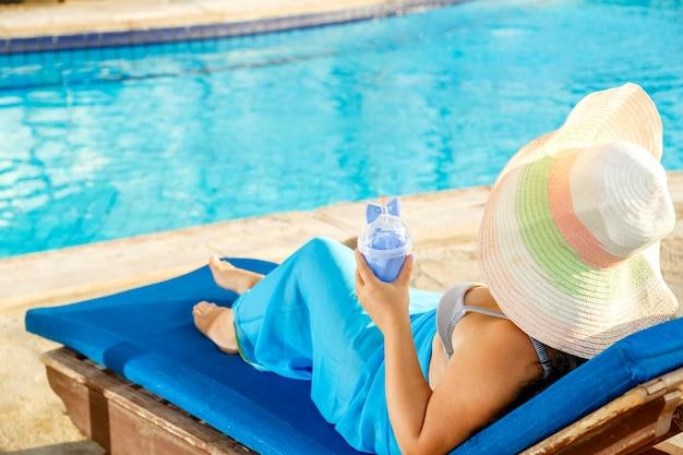 Een lachende brunette vrouw in een pareo badpak en hoed ligt op een ligstoel bij het zwembad en drinkt een cocktail. horizontale foto