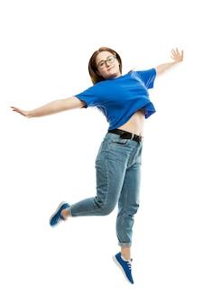 Een lachende dikke jonge vrouw in een blauw mouwloos onderhemd en spijkerbroek springt
