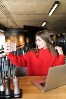 Een lachende freelancer-vrouw maakt een selfie aan de telefoon of voert een videogesprek, een werkdag van een vrije jonge vrouw of een student met een laptop.