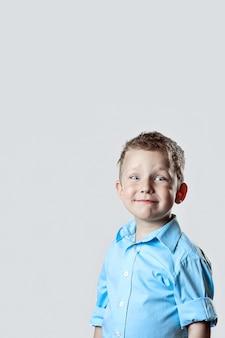 Een lachende gelukkige jongen in blauw shirt op licht