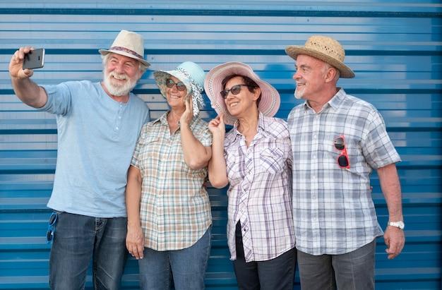Een lachende groep van vier mensen in vriendschap met strohoeden, samen kijkend naar smartphone voor een selfie. zorgeloze senior vrouwen en mannen genieten van pensioen