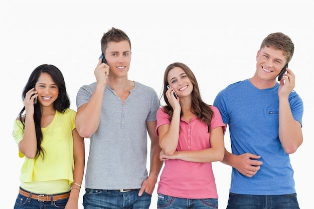 Een lachende groep vrienden belt terwijl ze in de camera kijkt