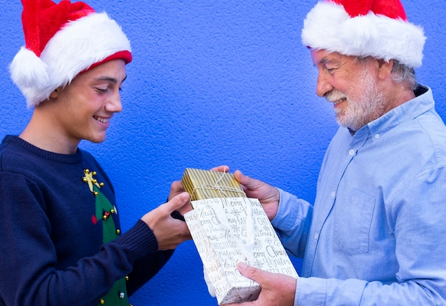 Een lachende grootvader met wit haar en een witte baard biedt een kerstcadeau aan zijn tienerkleinzoon die een kersttrui draagt. staande tegen een blauwe muur achtergrond