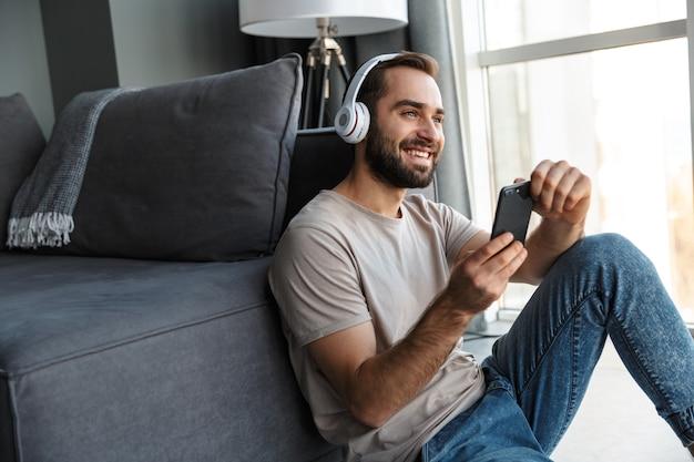 Een lachende jonge man binnenshuis luisteren muziek met koptelefoon zitten op de vloer chatten via de mobiele telefoon.