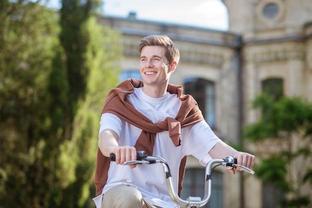 Een lachende jongeman in een ehite-t-shirt op een fiets