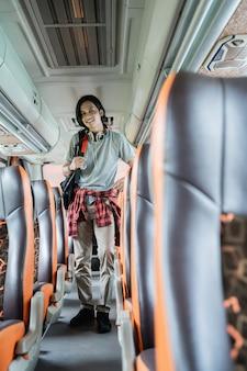 Een lachende jongeman met een rugzak en koptelefoon staat tussen de stoelen in de bus
