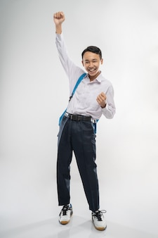 Een lachende jongen draagt een schooluniform en draagt een rugzak en steekt zijn hand op
