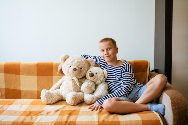 Een lachende jongen in gestreept t-shirt en blauwe korte broek zit op de bank en knuffelt knuffelbeer schattig portret van...