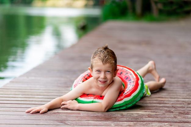 Een lachende jongen met een cirkel in de vorm van een watermeloen ligt in de zomer op het meer