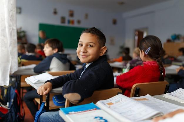 Een lachende jongen op zijn eerste schooldag