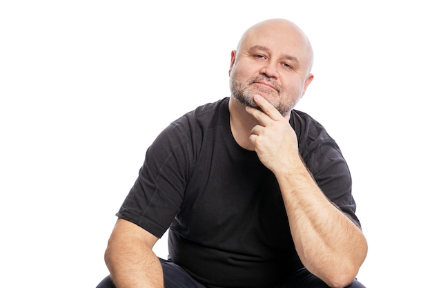 Een lachende kale man van middelbare leeftijd in een zwart t-shirt zit. over wit wordt geïsoleerd.
