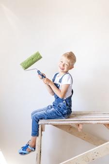 Een lachende kind bouwer zit op een bouwladder in een appartement met witte muren en houdt een kap voor het schilderen van muren, een plek voor tekst, een reparatie-concept