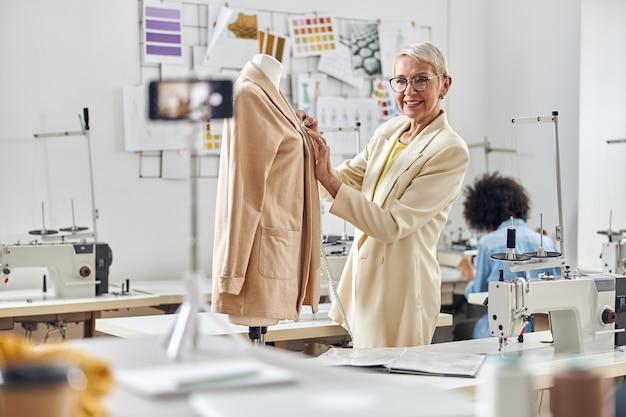 Een lachende kleermaker laat een nieuwe beige jas zien die video opneemt terwijl de afro-amerikaanse naaister aan de tafel zit