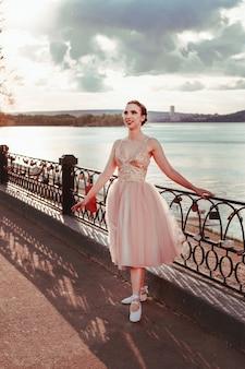 Een lachende lachende ballerina in een roze zijden jurk poseert terwijl ze zich vasthoudt aan het hek van het pad
