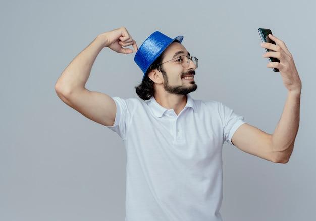 Een lachende man met een bril en een blauwe hoed neemt een selfie en zet de vinger op de hoed die op een witte muur wordt geïsoleerd