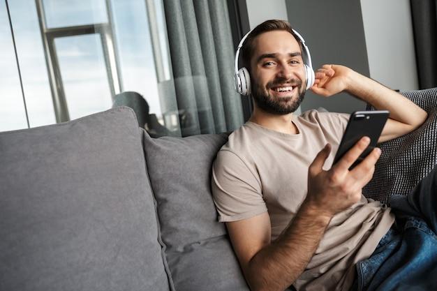 Een lachende optimistische jonge knappe man binnenshuis thuis op de bank muziek luisteren met een koptelefoon met behulp van mobiele telefoon.