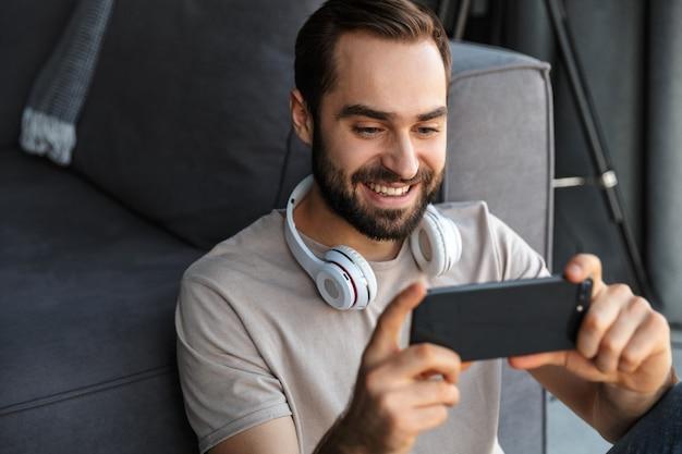 Een lachende optimistische jongeman binnenshuis speelt spelletjes met de mobiele telefoon op de vloer.
