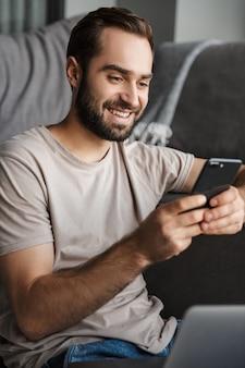 Een lachende positieve jonge man binnenshuis thuis op de bank met behulp van laptopcomputer chatten via de mobiele telefoon.