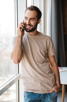 Een lachende positieve jonge man binnenshuis thuis praten via de mobiele telefoon.